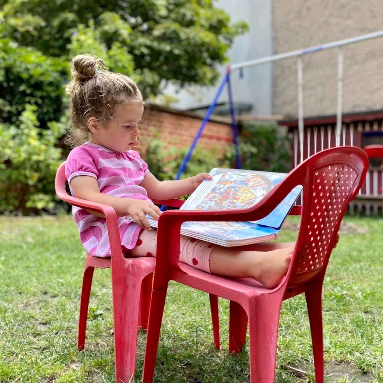 Child sitting on a chair in the garden reading a book